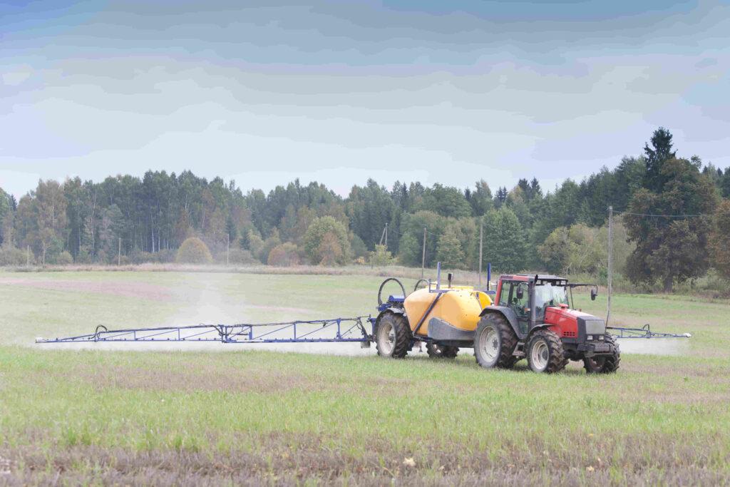 tractor rociando insecticidas agrícola en campo de argentina